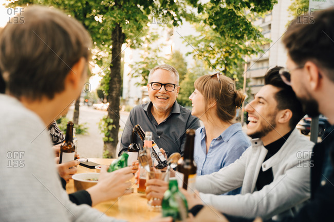 Portrait of happy mature male sitting with friends and enjoying at social gathering