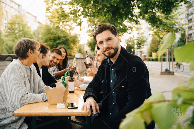 Portrait of smiling young male sitting with friends and enjoying at social gathering