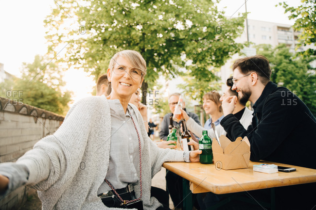 Portrait of happy mature female sitting with friends and enjoying at social gathering