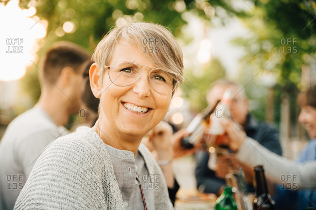 Portrait of happy mature female sitting with friends at social gathering