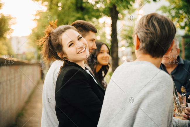 Portrait of smiling young female sitting with friends and enjoying at social gathering