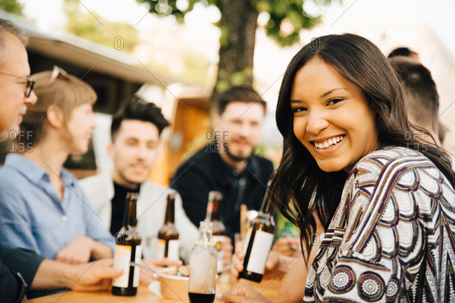 Portrait of smiling young woman sitting with friends and enjoying at social gathering