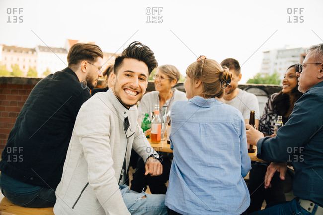 Portrait of happy man sitting with friends and enjoying at social gathering