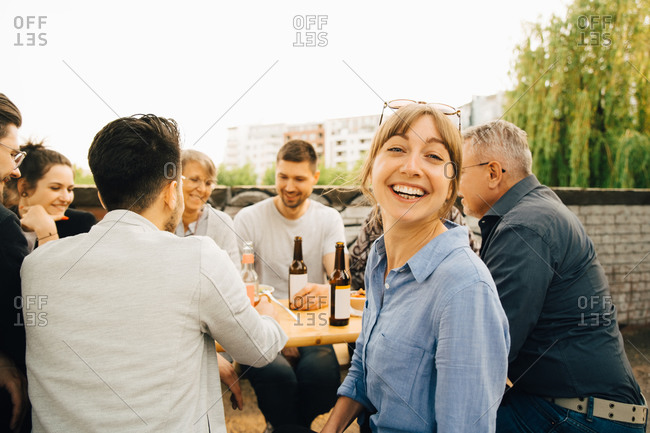 Portrait of smiling female sitting with friends and enjoying at social gathering