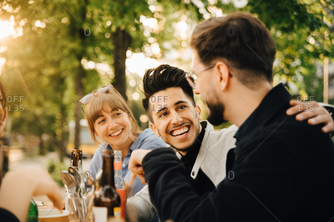 Happy young man sitting by male and female friend at social gathering