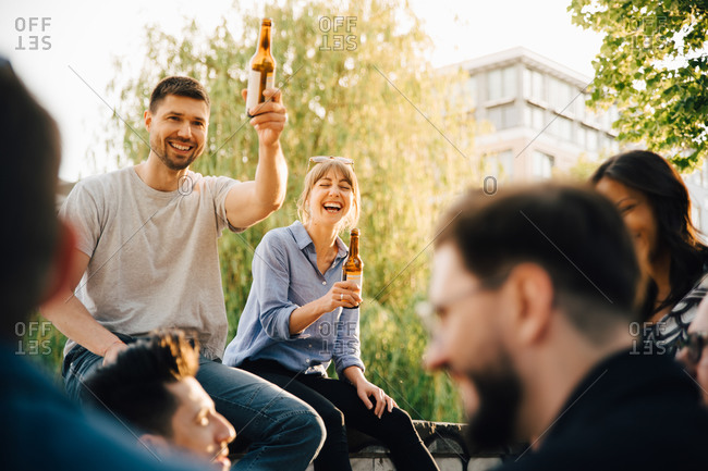 Male and female friends laughing while sitting at social gathering