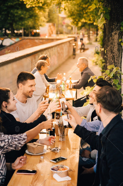 Happy male and female friends toasting beer while sitting in garden