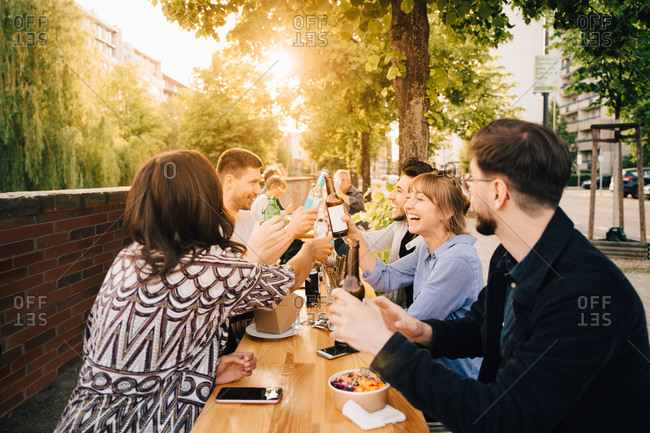 Male and female friends toasting while sitting at social gathering