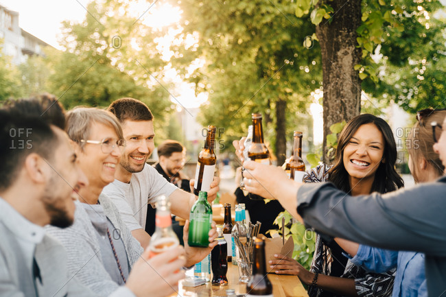 Male and female friends laughing while toasting with drinks at social gathering