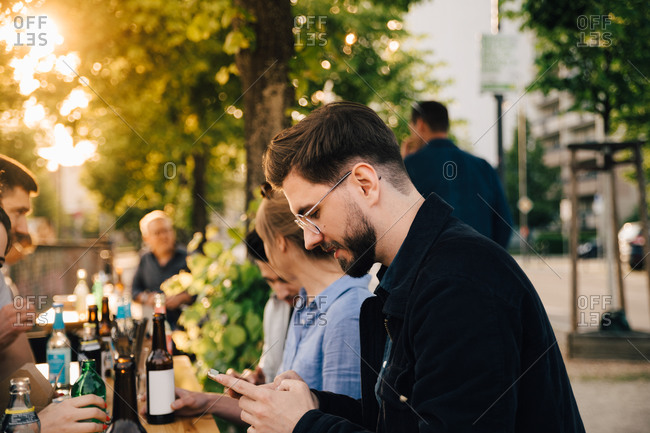 Young man using phone while sitting female friend at social gathering