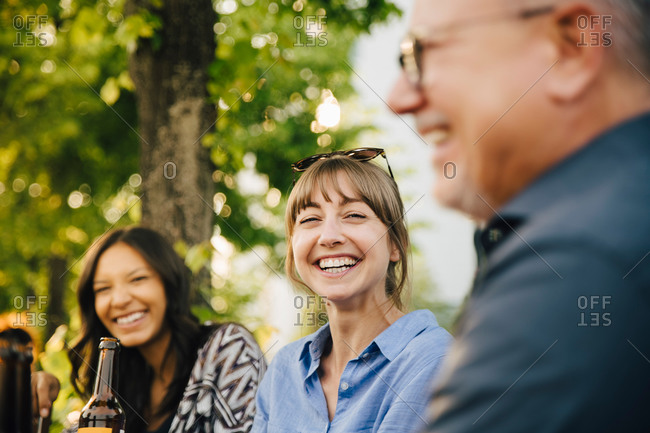 Male and female friends laughing at social gathering