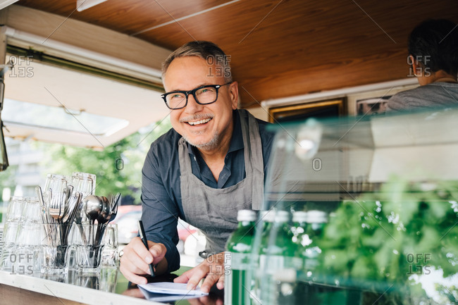 Happy mature owner standing with pen standing in food truck