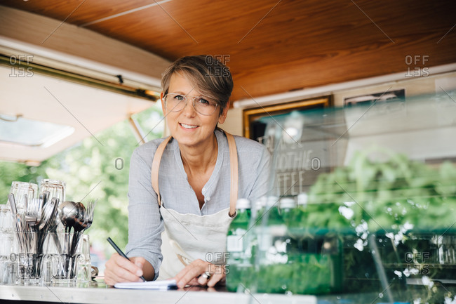 Portrait of mature owner taking order while standing in food truck