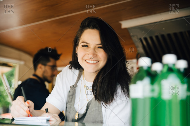 Portrait of happy female owner writing order in food truck while male coworker working in background