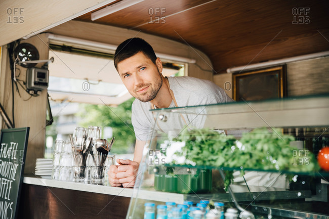 Portrait of male owner standing in food truck