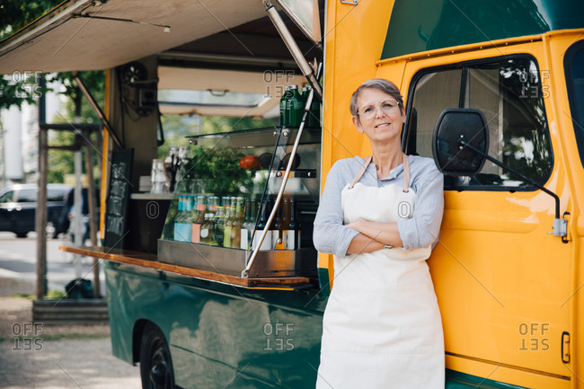Portrait of mature owner with arms crossed standing against food truck