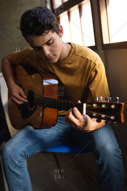 Front view close up of a Caucasian musician teenage boy sitting and playing an acoustic guitar in a high school