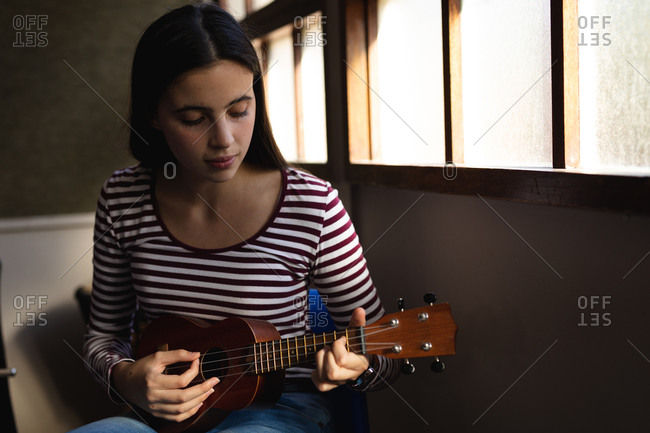 Portrait of a Caucasian musician teenage girl sitting by a window, looking down and playing a ukulele in a high school