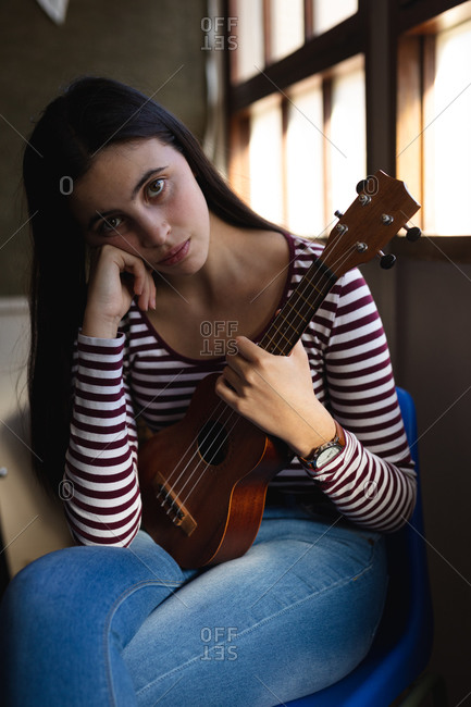 Portrait of a Caucasian musician teenage girl sitting by a window, looking to camera and holding a ukulele in a high school