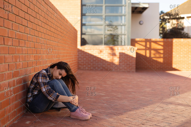 Side view of a Caucasian sad teenage girl sitting on the ground alone in a schoolyard  in a high school