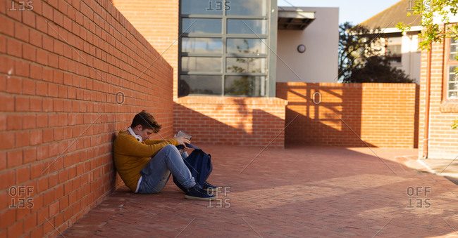 Side view of a sad lonely bullied Caucasian isolated teenage boy sitting on the ground alone in a schoolyard reading