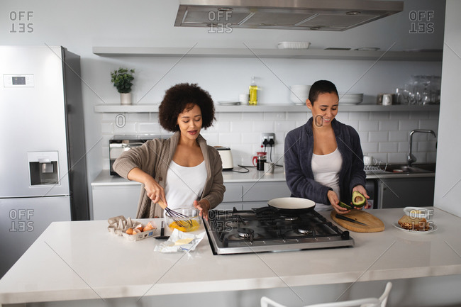 Front view of mixed race female couple relaxing at home, standing in the kitchen preparing breakfast together and smiling together