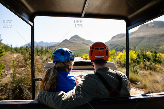 Rear view of Caucasian couple enjoying time in nature together, in zip lining equipment sitting in a car on a sunny day in mountains