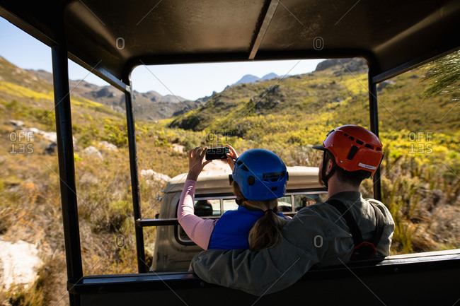 Rear view of Caucasian couple enjoying time in nature together, in zip lining equipment sitting in a car, the woman taking photos with smartphone on a sunny day in mountains