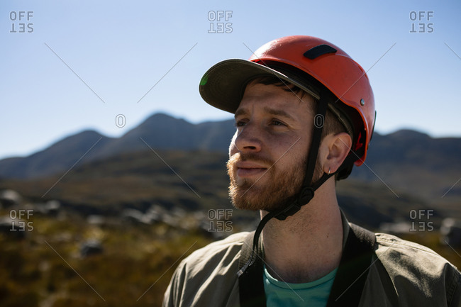 Front view close up at Caucasian man enjoying time in nature, wearing zip lining equipment on a sunny day in mountains
