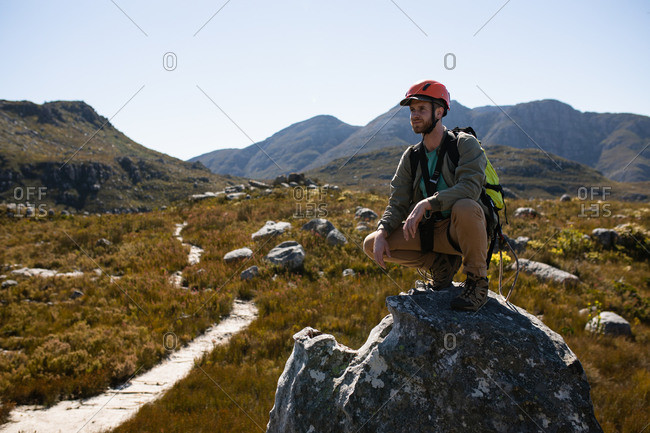 Side view of Caucasian man enjoying time in nature, wearing zip lining equipment, hiking, squatting on a rock on a sunny day in mountains
