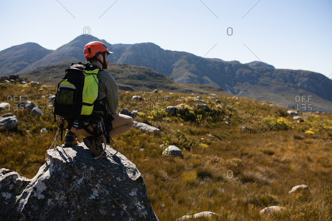 Rear view of Caucasian man enjoying time in nature, wearing zip lining equipment, hiking, squatting on a rock on a sunny day in mountains