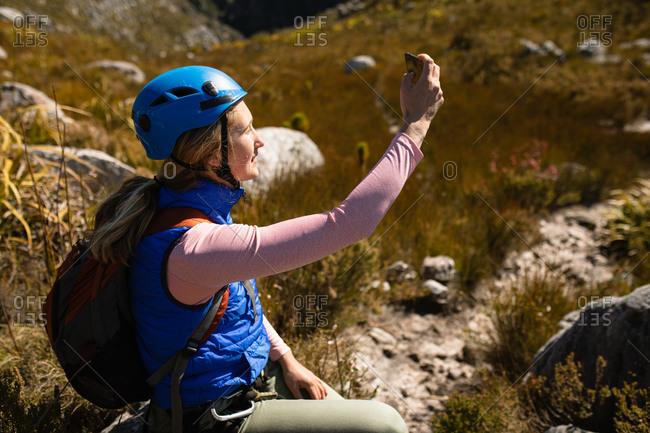 Side view of Caucasian woman enjoying time in nature, in zip lining equipment, sitting, taking photos with smartphone on a sunny day in mountains