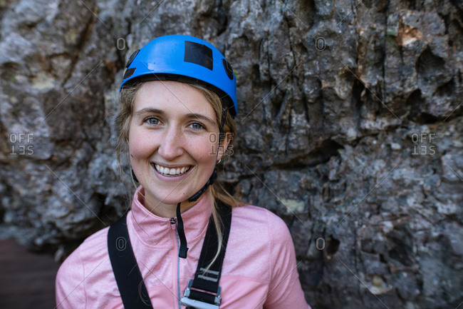 Portrait of Caucasian woman enjoying time in nature, wearing zip lining equipment, smiling on a sunny day in mountains. Fun adventure vacation weekend.