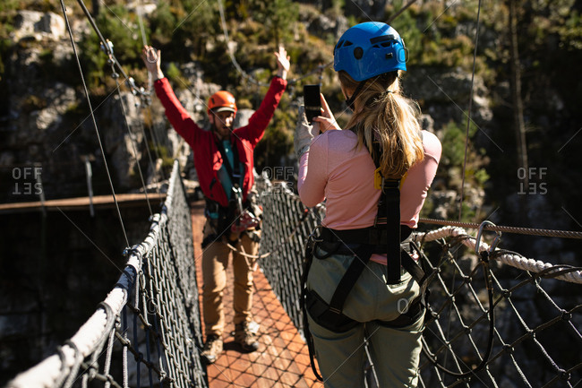 Rear view of Caucasian couple enjoying time in nature, wearing zip lining equipment, the woman taking pictures of a man with a smartphone on a sunny day in mountains