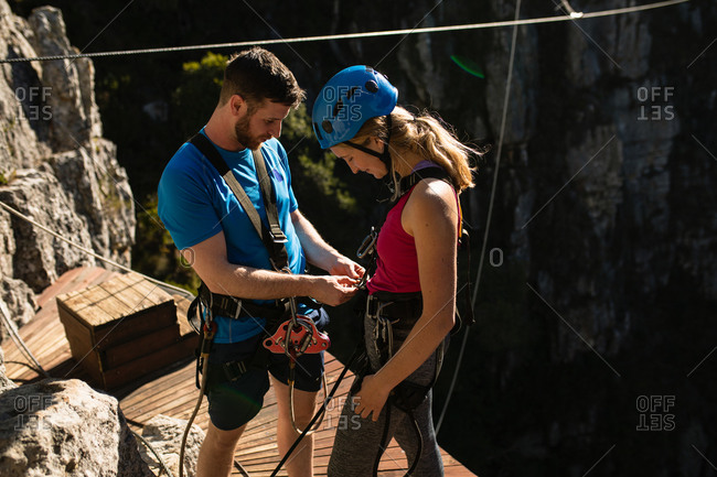 Side view of Caucasian couple enjoying time in nature together, wearing zip lining equipment, the man is helping the woman to put the zip line equipment on, the woman is smiling, on a sunny day in mountains