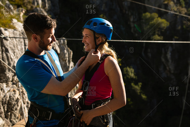 Side view of Caucasian couple enjoying time in nature together, wearing zip lining equipment, the man is putting helmet on the woman, smiling on a sunny day in mountains