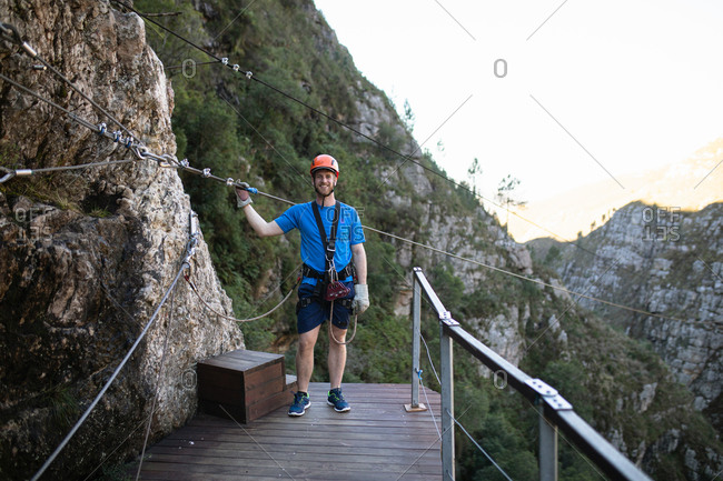 Portrait of Caucasian man enjoying time in nature, wearing zip lining equipment, holding the zip line rope, on a sunny day in mountains