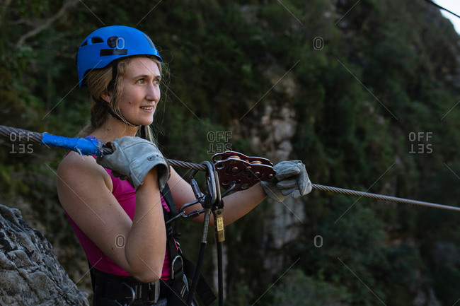 Side view of Caucasian woman enjoying time in nature, wearing zip lining equipment, smiling and holding the zip line rope on a sunny day in mountains