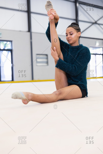 Side view of teenage mixed race female gymnast practicing at the gym, stretching her leg and warming up. Gymnasts training hard for competition.