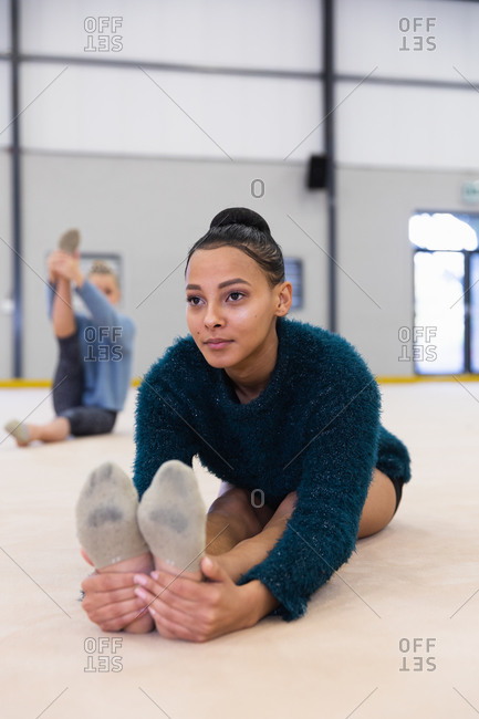 Front view of mixed race and Caucasian teenage female gymnasts practicing at the gym, stretching and warming up. Gymnasts training hard for competition.