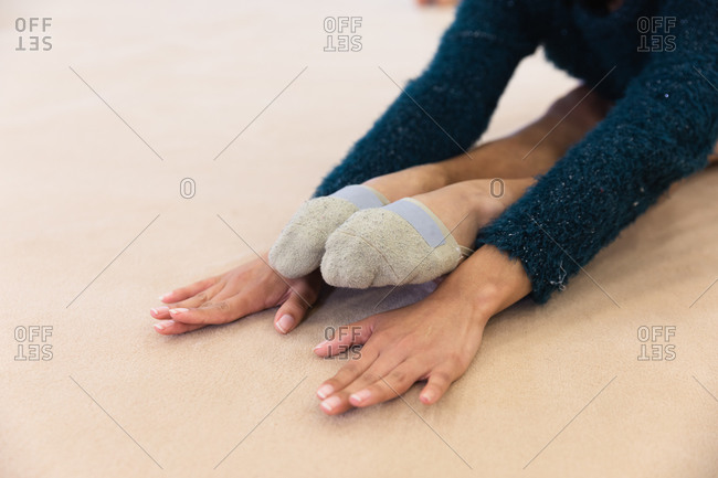 Close up of hands and legs of teenage mixed race female gymnast practicing at the gym, stretching and warming up