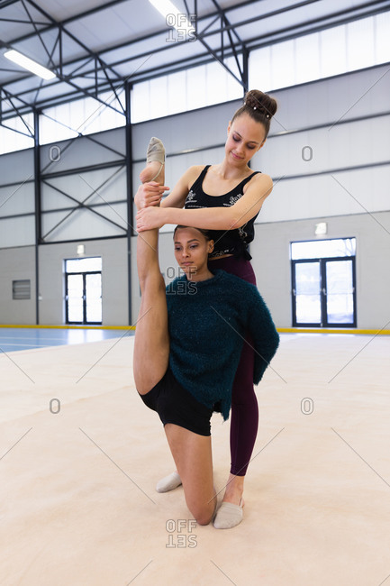Front view of Caucasian and mixed race female gymnasts practicing at the gym together, one girl helping the other to stretch her legs