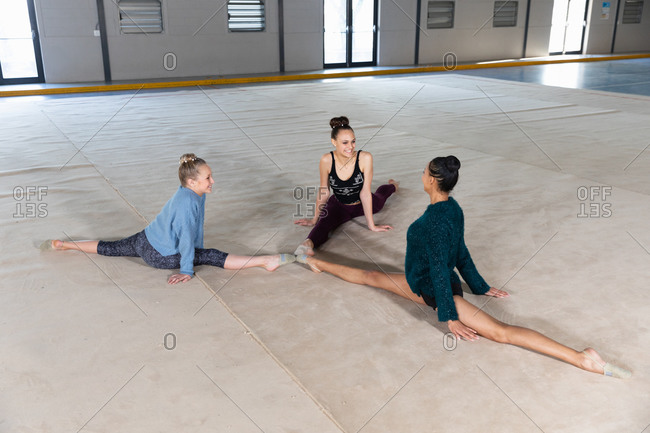 High angle view of one teenage mixed race and two Caucasian female gymnasts practicing at the gym together, doing splits, touching each other toes, stretching and smiling to each other