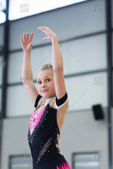 Side view close up of happy teenage Caucasian female gymnast performing at sports hall, standing with arms up, wearing pink, black and beige leotard