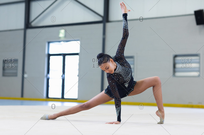 Front view of teenage mixed race female gymnast performing at sports hall, standing and leaning with one hand on the floor, wearing black leotard