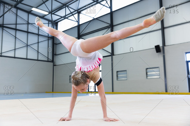 Rear view of teenage Caucasian female gymnast performing at sports hall, doing handstand and split, wearing white, pink and beige leotard