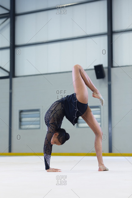 Side view of teenage mixed race female gymnast performing at sports hall, bending backwards with hands on the floor, wearing black leotard