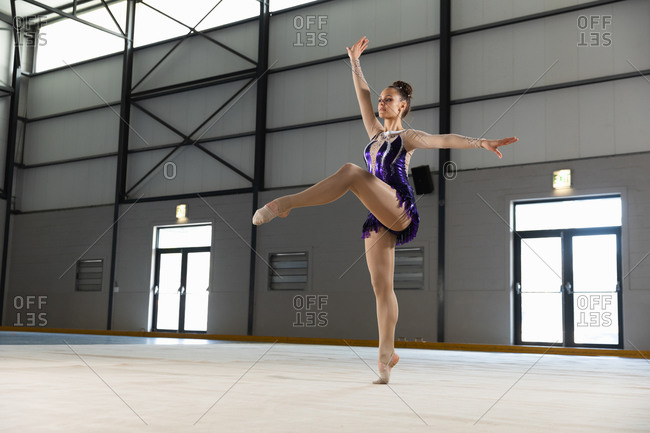 Side view of teenage Caucasian female gymnast performing at the gym, standing on one leg and arms stretched out, wearing purple leotard