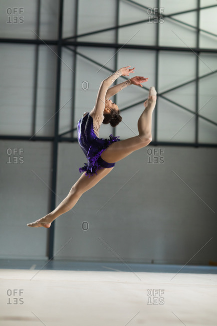 Side view of teenage Caucasian female gymnast performing at the gym, jumping with arms stretched up, wearing purple leotard. Gymnasts training hard for competition.