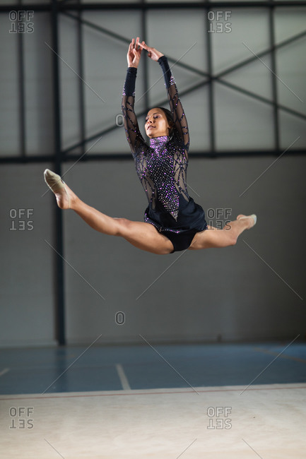 Front view of teenage mixed race female gymnast performing at the gym, jumping and doing split, wearing black and purple leotard